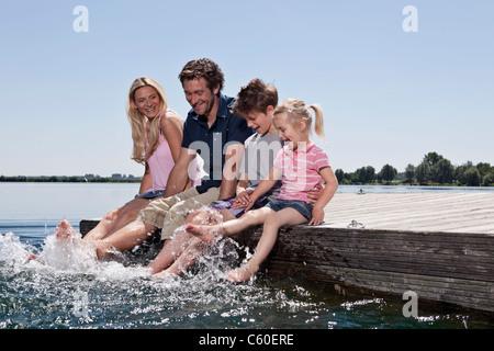 Famiglia insieme giocando sul dock Foto Stock