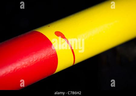 Primo piano di rosso e giallo striato braccio metallico con errore di verniciatura Foto Stock