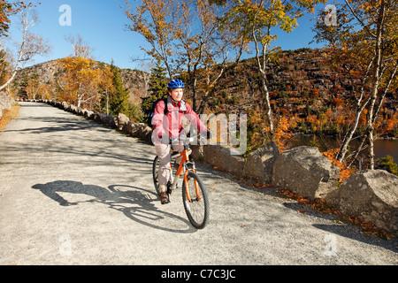 Woman mountain bike sulla ghiaia storica strada carrozzabile, isola di Mount Desert, Parco Nazionale di Acadia, Foto Stock