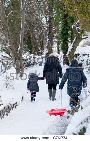 Una famiglia di tre persone, camminando lungo una coperta di neve bridleway. Foto Stock