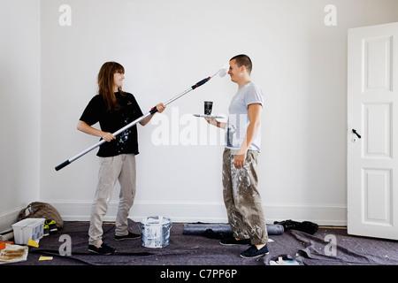 Giovane pittura pareti della nuova casa Foto Stock