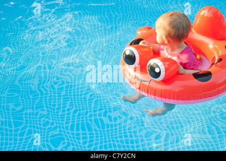 Bambino piccolo nel dispositivo di galleggiamento che guarda lontano mentre galleggia in una piscina da solo Foto Stock