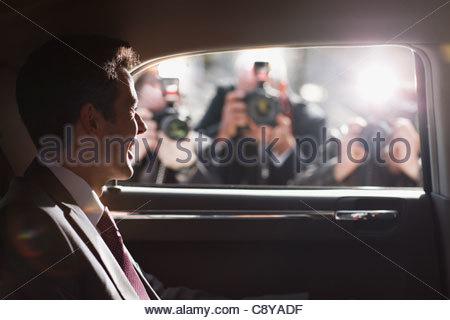 Politico sorridere per paparazzi in backseat di auto Foto Stock