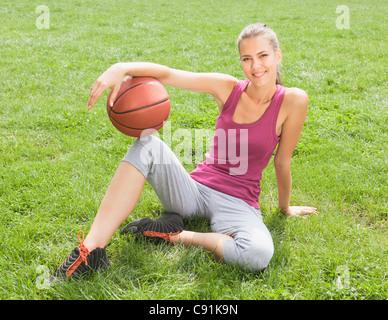 Donna che mantiene la pallacanestro di erba Foto Stock