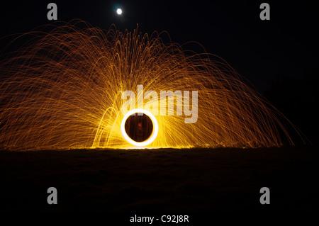 La lana di acciaio la filatura, creazione di splendide striature circolare di luce dorata dalla combustione di filo Foto Stock
