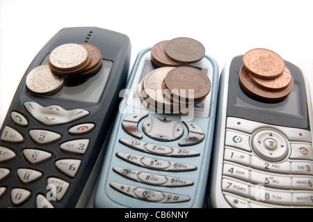 Tre telefoni cellulari con il denaro Foto Stock