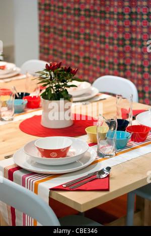 Bianco, arancio, rosso, giallo, turchese e blu decorato tavolo da pranzo in ristorante Foto Stock
