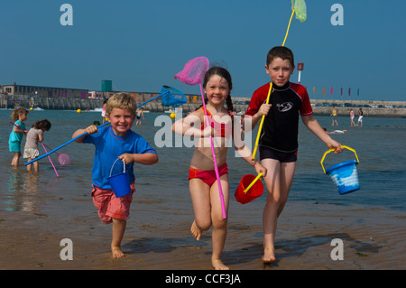 I bambini con benne e reti da pesca giocando a Margate Beach. Isola di Thanet. Kent England Foto Stock