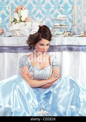 Bella donna asiatica con un sulky pout seduta sul pavimento accanto a una tabella di partito Foto Stock