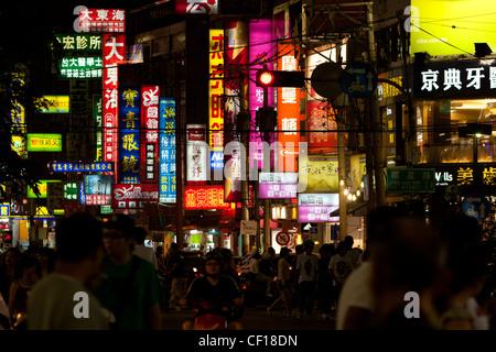 Una strada affollata scena mostrando illuminazione infinita di cartelloni e people shopping notturno in Feng Chia Foto Stock