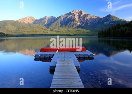 Red canoa sul dock a Lago Piramide con la piramide, di montagna del Parco Nazionale di Jasper, Alberta, Canada. Foto Stock