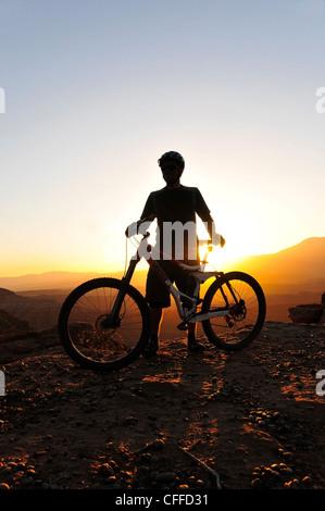 Una silhouette di un mountain biker al tramonto su Gooseberry Mesa nel sud dello Utah. Foto Stock