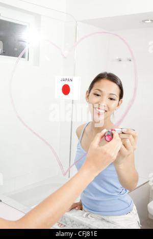 Giovane donna cuore di disegno con il rossetto sullo specchio Foto Stock