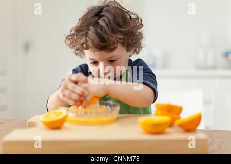 Ragazzo la spremitura di arance per fare succo Foto Stock