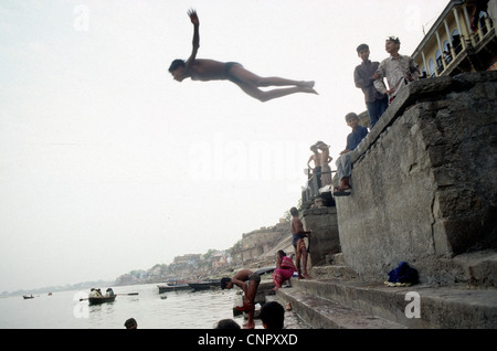 Ragazzo indiano di saltare sul fiume Gange a indiana antica città di Benares (Varanasi), Uttar Pradesh, India. Foto Stock