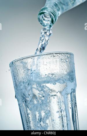 Close-up di acqua minerale che viene versato in un bicchiere. Foto Stock
