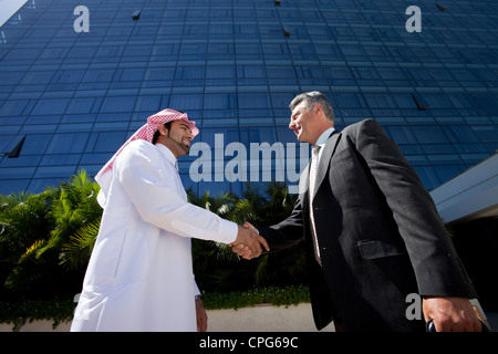Imprenditore arabo e imprenditore occidentale stringono le mani nella parte anteriore dell'edificio degli uffici. Foto Stock