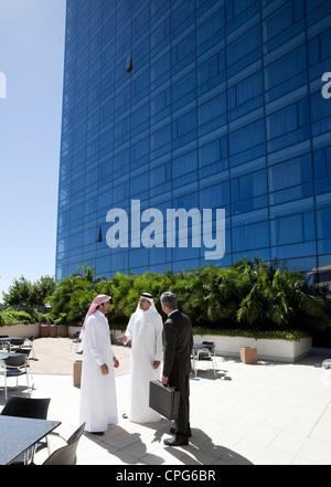 Tre uomini di affari di parlare di fronte all edificio per uffici. Foto Stock