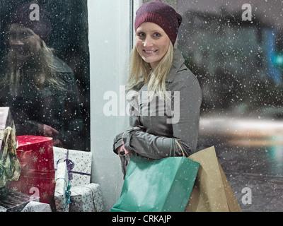 La donna il trasporto delle borse della spesa in snow Foto Stock