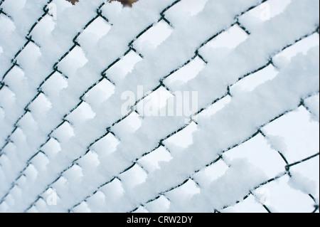 Neve su una catena collegamento recinto Foto Stock