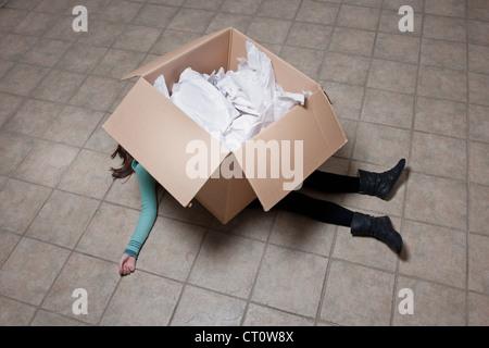 Ragazza adolescente giacente sotto la scatola di cartone Foto Stock