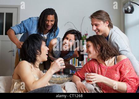 Gli amici di ridere insieme in salotto Foto Stock