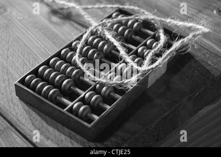 Un legno di antiquariato abacus. su una panca in legno, la fotografia in bianco e nero Foto Stock