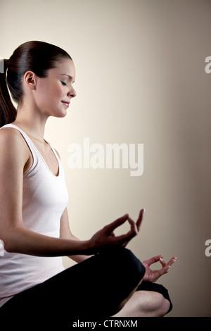 Una giovane donna meditando a occhi chiusi Foto Stock