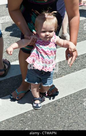 Adorabili poco bionda toddler prendendo il primo bambino passi con il supporto dalla sua mamma sulla bella giornata Foto Stock