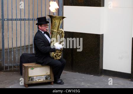 L'uomo musicista di strada con una tuba che spara fuoco, London, England, Regno Unito Foto Stock