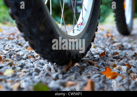 Close-up di ruote di bicicletta sul sentiero di ghiaia Foto Stock