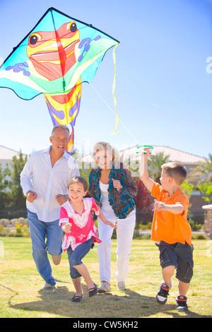Famiglia volare un aquilone in un parco Foto Stock
