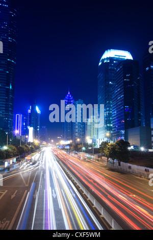 Sentieri di luce sulla strada con la costruzione di sfondo Foto Stock