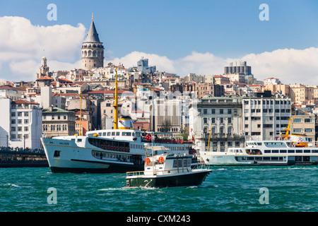 Turchia, Istanbul. Passeggeri delle navi e barche a vela sul Golden Horn con Torre di Galata in background Foto Stock