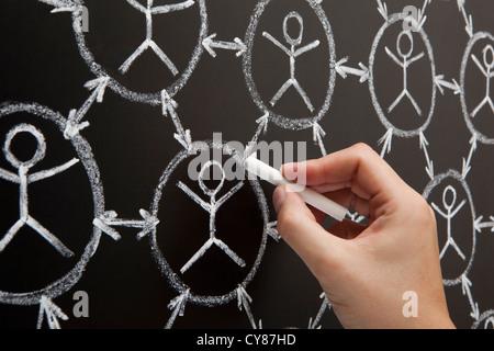 La mano che mostra il social networking concept realizzato con il bianco gesso su una lavagna Foto Stock