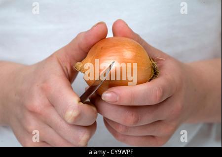 Sbucciare la cipolla. donna utilizzando un coltello per sbucciare una cipolla tenuto nelle sue mani Foto Stock