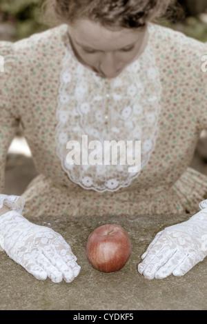 Una ragazza in un abito vittoriano è seduto davanti a un Apple Foto Stock