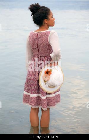 Una ragazza in un abito floreale tenendo un cappello di paglia Foto Stock
