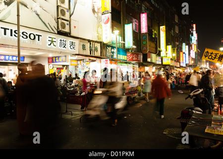 Una strada affollata scena mostrando illuminazione infinita di cartelloni e people shopping notturno in Huaxi Street Foto Stock