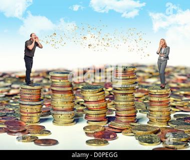 L uomo e la donna e denaro talk su pali di monete Foto Stock