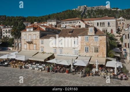 Caffè nella piazza principale, dominato dall'antica fortezza, nella città medievale di Hvar Hvar, isola della Dalmazia, Foto Stock