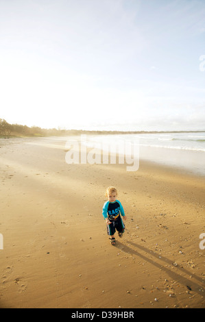 Piccolo ragazzo in costume da bagno blu / sunsuit su una spiaggia da sola Foto Stock