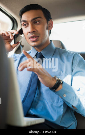 Imprenditore Bengali usando un computer portatile e a parlare su un telefono cellulare in un'automobile Foto Stock