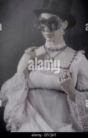 Una donna in un periodo vestito con un cappello a cilindro e una maschera nera Foto Stock