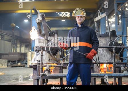 Lavoratore azienda pistola a fiamma in fonderia Foto Stock