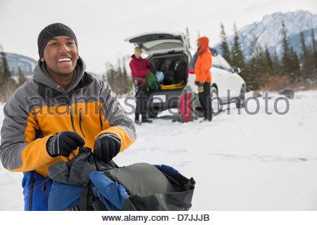 Uomo sorridente con gli amici preparando per escursione invernale in montagna Foto Stock