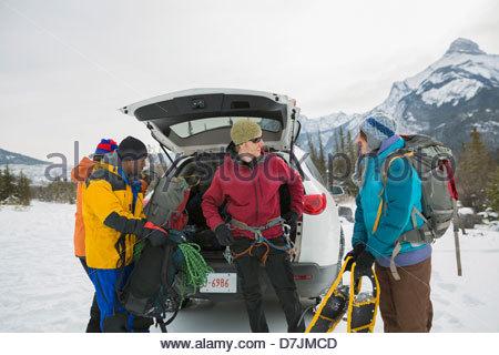 Gruppo di amici preparando per escursioni con le racchette da neve in montagna Foto Stock