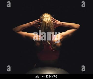 Donna Fitness facendo stomaco scricchiola mentre giaceva sulla sfera di yoga Foto Stock