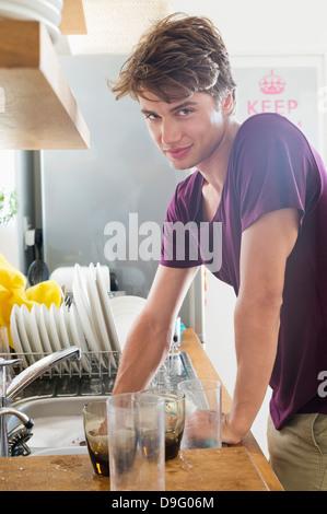 L'uomo lavaggio piatti nella sua cucina Foto Stock