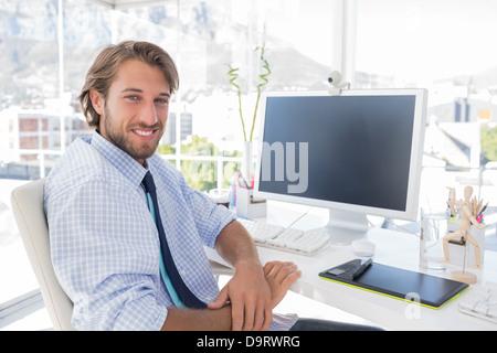 Designer sorridente seduto alla sua scrivania Foto Stock